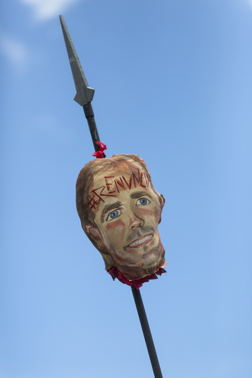 """Demonstrators carry a image representing the head of Governor Ricardo Rossello on a pike, with an inscription on its forehead that reads in Spanish """"R..."""