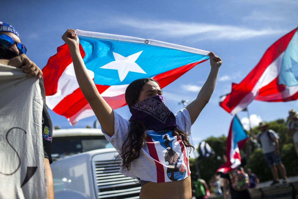 Demonstrators join a protest to demand the resignation of Governor Ricardo Rossello from office, in San Juan, Puerto Rico, Monday, July 22, 2019. Prot...