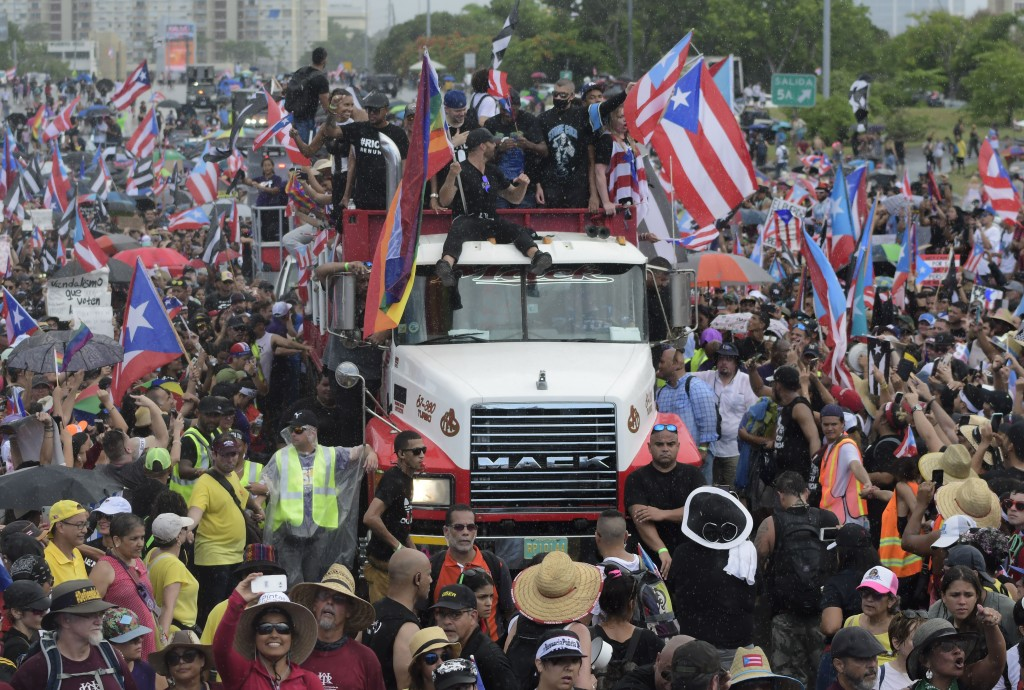 Puerto Rican singer Ricky Martin, front atop truck, participates with other local celebrities in a protest demanding the resignation of governor Ricar...