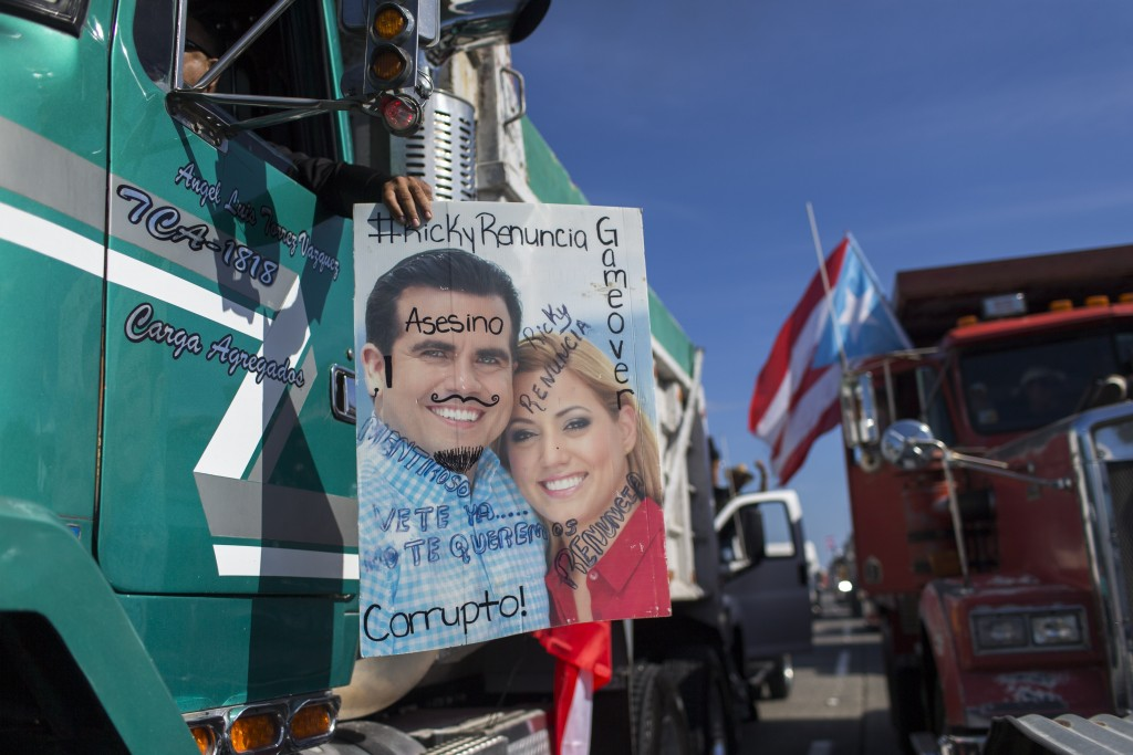 """Demonstrators carry a defaced poster of Governor Ricardo Rossello and his wife, with inscriptions that read in Spanish """"Corrupt, murderer, Ricky quit,..."""