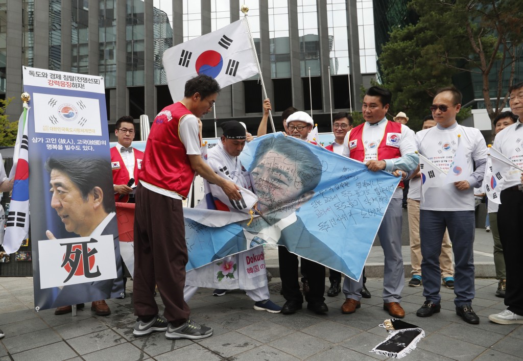 A South Korean protester uses scissors to cut an image of Japanese Prime Minister Shinzo Abe during a rally denouncing the Japanese government's decis...