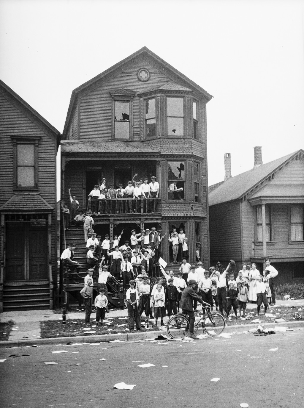 In this 1919 photo provided by the Chicago History Museum, a crowd gathers at a house that has been vandalized and looted during the race riots in Chi...