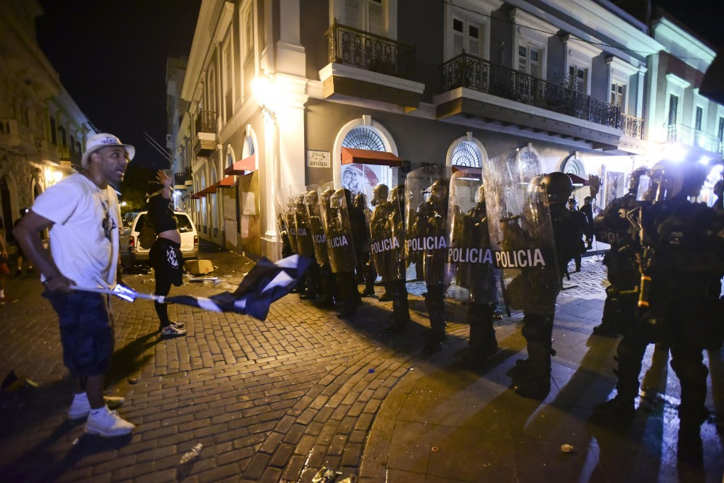 Demonstrators stand in front of riot control units during clashes in San Juan, Puerto Rico, Monday, July 22, 2019. Protesters are demanding Gov. Ricar...