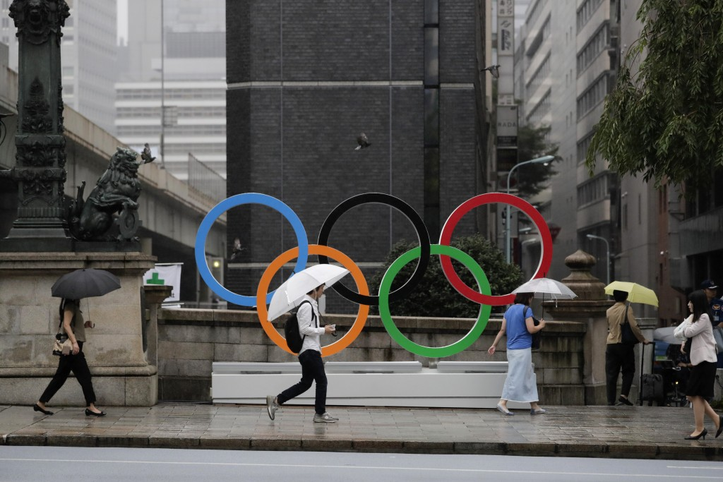 Commuters walk past the Olympic Rings Tuesday, July 23, 2019, in Tokyo. To mark the year-to-go mark, the gold, silver and bronze Olympic medals are to...
