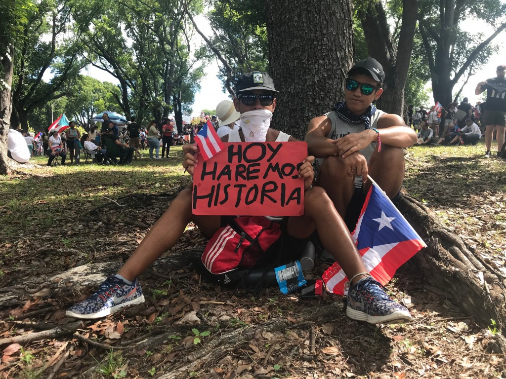 """Giovanni Andre Correa, a 17-year-old high school student, holds a sign the reads in Spanish """"Today we will make history"""" as he sits next to his 20-yea..."""