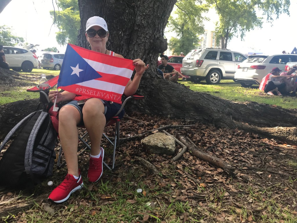 Lydia Hernandez, a 62-year-old retiree, poses for a photo with a Puerto Rico flag, during a protest to demand the resignation of Governor Ricardo Ross...