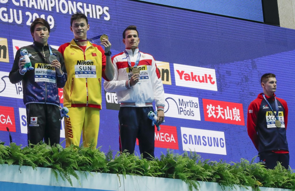 Britain's bronze medalist Duncan Scott, right, refuses to stand with gold medalist China's Sun Yang, second left, as silver winner Japan's Katsuhiro M...