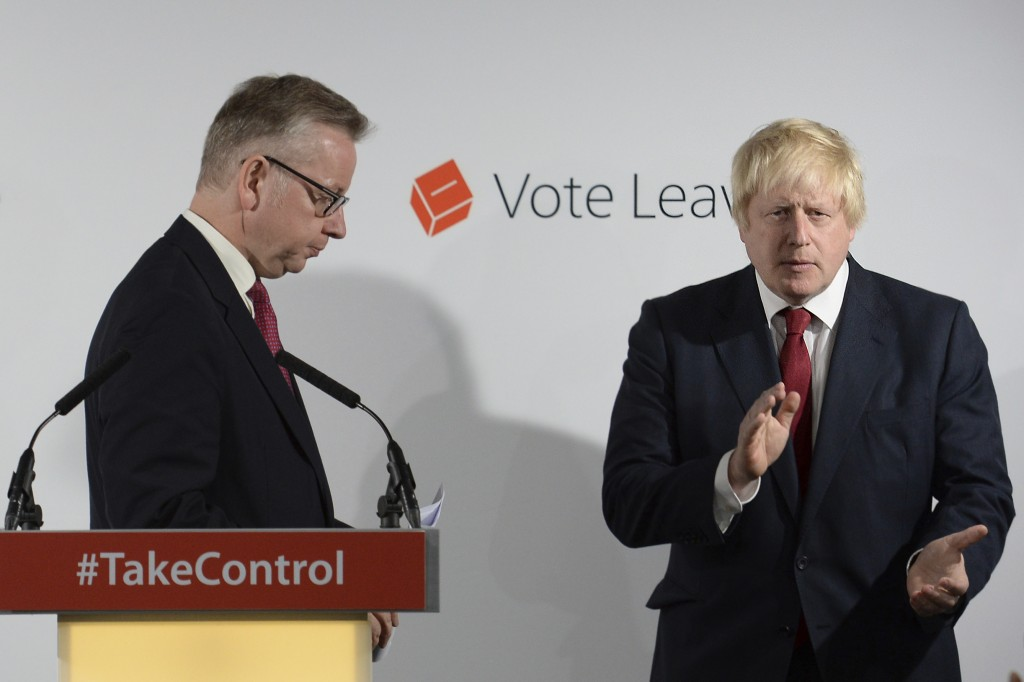 FILE - In this Friday June 24, 2016 file photo Vote Leave campaigners Michael Gove, left, leaves the lectern as Boris Johnson applauds at a press conf...