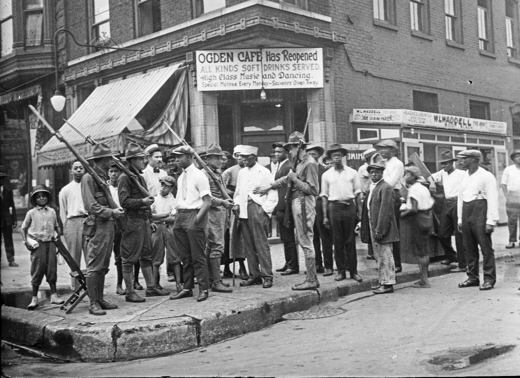 In this 1919 photo provided by Chicago History Museum, a crowd of men and armed National Guard stand in front of the Ogden Cafe during race riots in C...