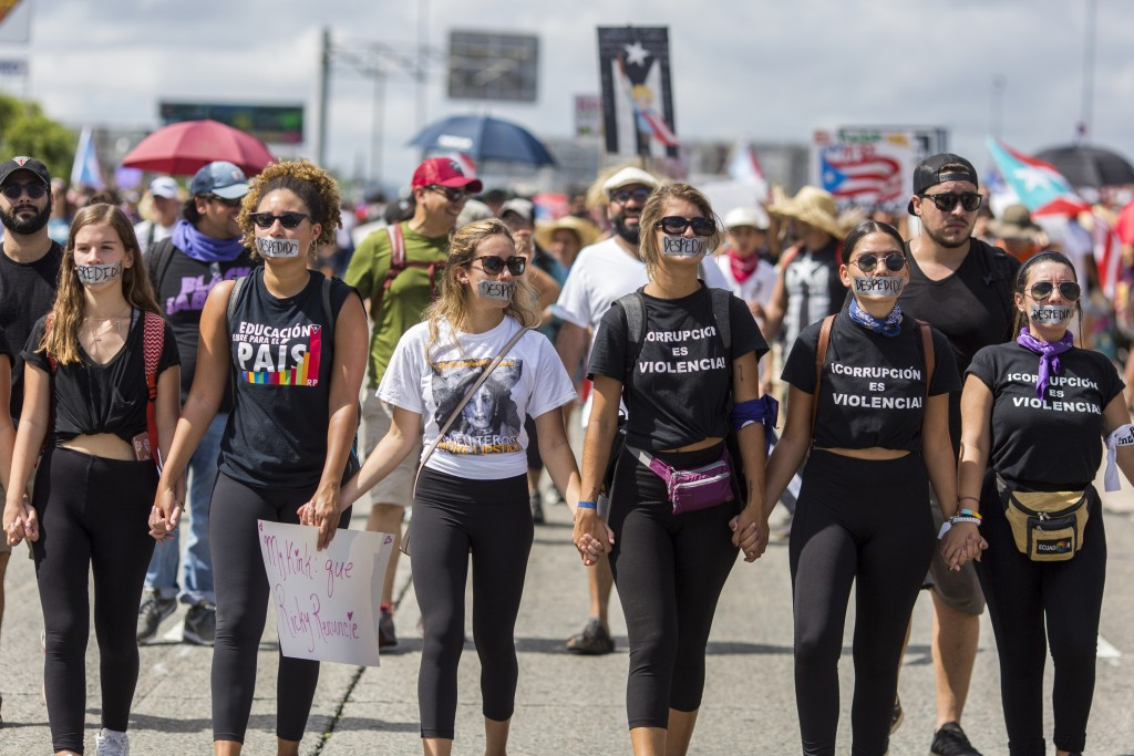 """Demonstrators with their mouths covered with a tape in which they wrote in Spanish """"fired"""" march on Las Americas highway demanding the resignation of ..."""