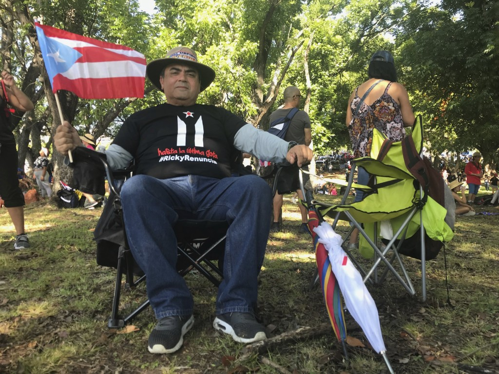 Jose Troche, a 64-year-old doctor from Yauco, sits under the shade in a beach chair as he waits for the protest march to demand the resignation of Gov...