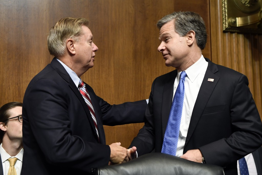 FBI Director Christopher Wray, right, talks with Senate Judiciary Committee Chairman Sen. Lindsey Graham, R-S.C., right, before he sits down to testif...