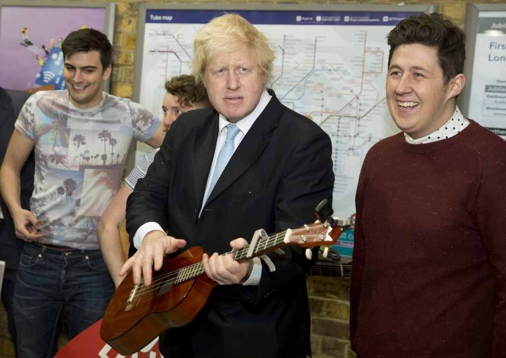 FILE - In this Monday, March 23, 2015 file photo Mayor of London Boris Johnson plays with a guitar in front of the busking band The Tailormade during ...