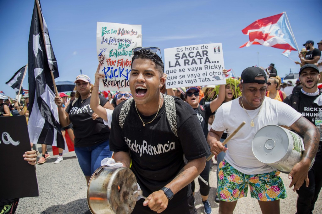 Demonstrators bang on pots and buckets as they march on Las Americas highway demanding the resignation of governor Ricardo Rossello, in San Juan, Puer...
