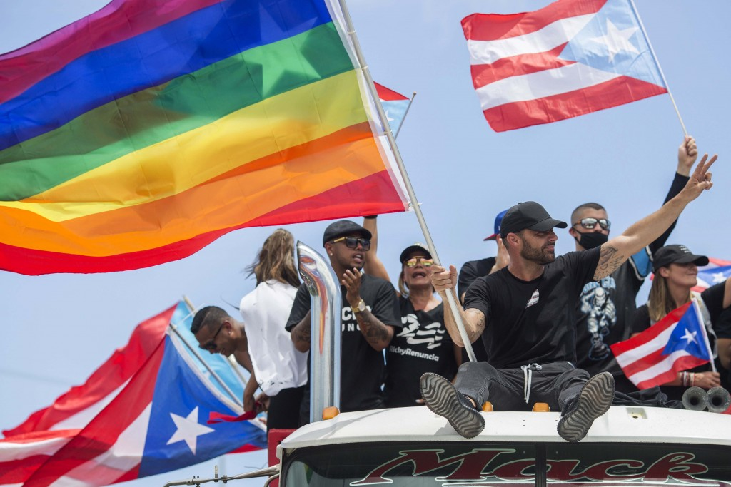 Ricky Martin, flying a gay pride flag, joins a protest to demand the resignation of Governor Ricardo Rossello from office, in San Juan, Puerto Rico, M...