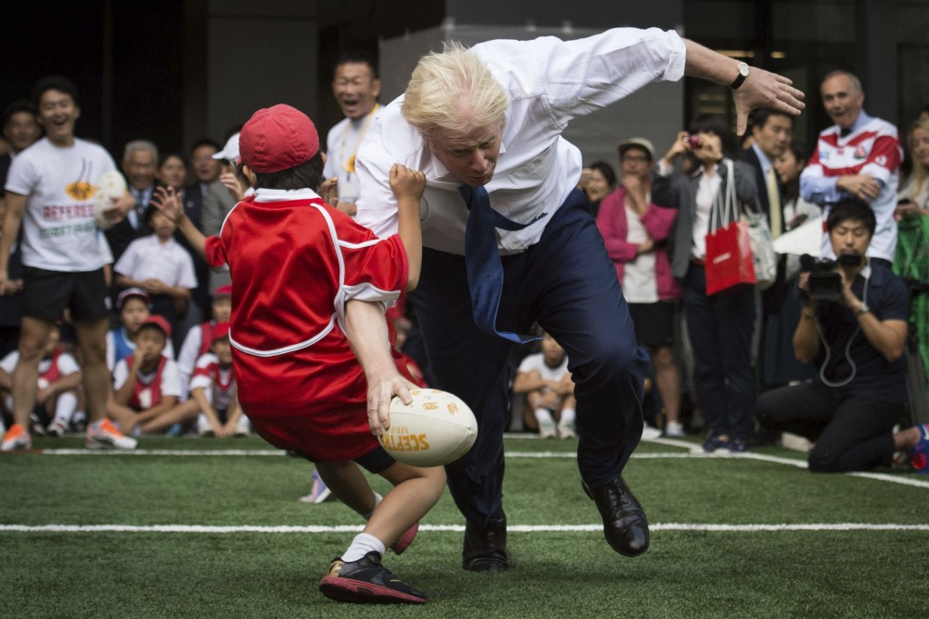 FILE - In this Oct. 15, 2015 file photo, Boris Johnson takes part in a Street Rugby tournament in a Tokyo street. Britain's new top diplomat is shaggy...