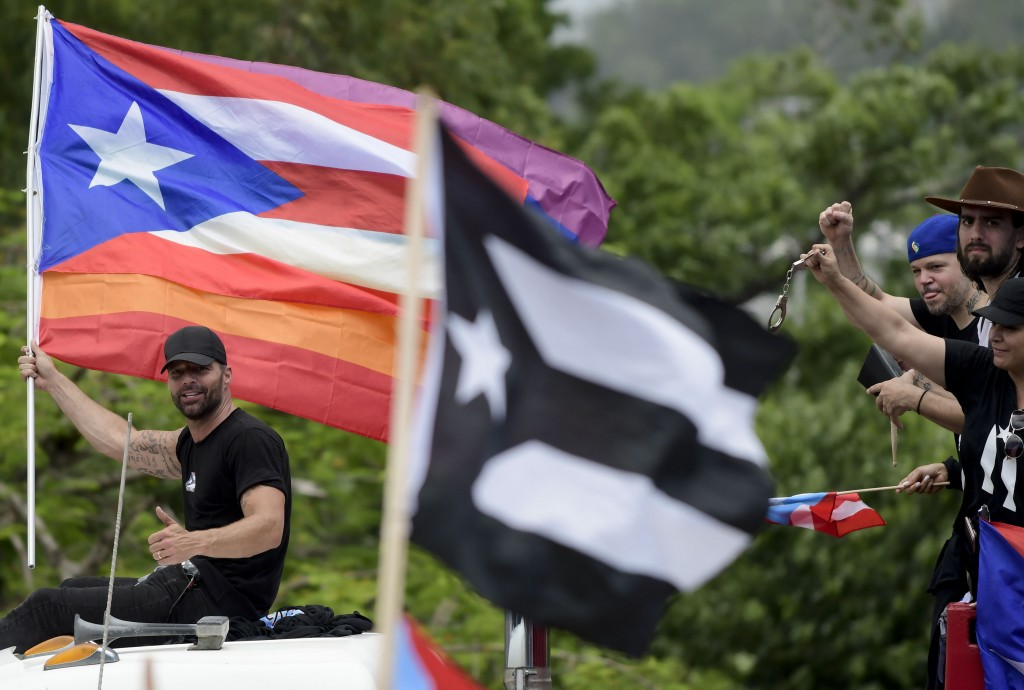 Puerto Rican singer Ricky Martin holds a Puerto Rico flag as he participates in a protest demanding the resignation of governor Ricardo Rossello, in S...