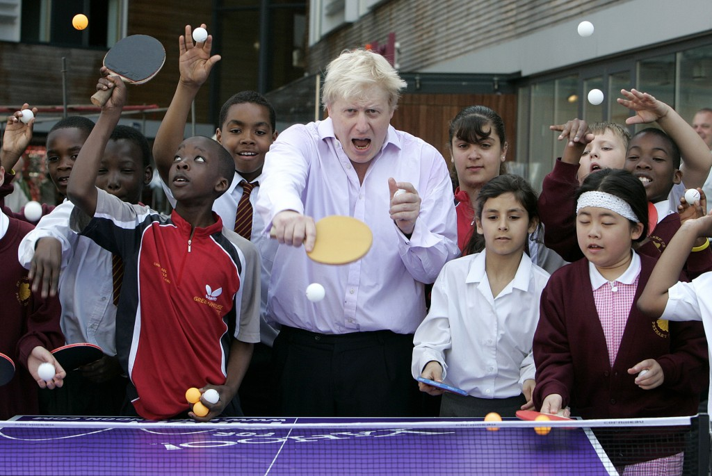 FILE - In this Friday, June 25, 2010 file photo, Mayor of London Boris Johnson, center, poses for photographers as he plays a game of table tennis wit...