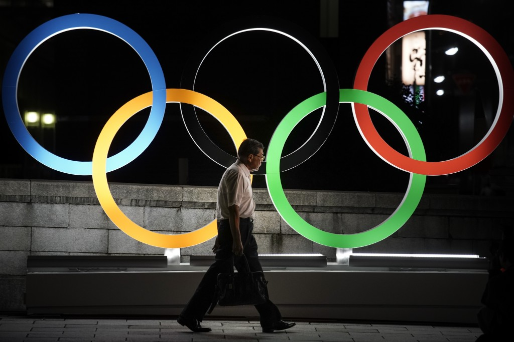 A man walks past the Olympic rings Tuesday, July 23, 2019, in Tokyo, as Japan marks a year-to-go until hosting the summer games with Olympic medals be...