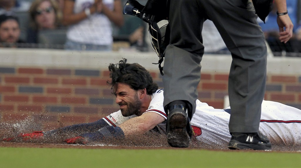 Atlanta Braves Dansby Swanson slides safely into home plate on a hit against the Kansas City Royals during the first inning of a baseball game Tuesday...