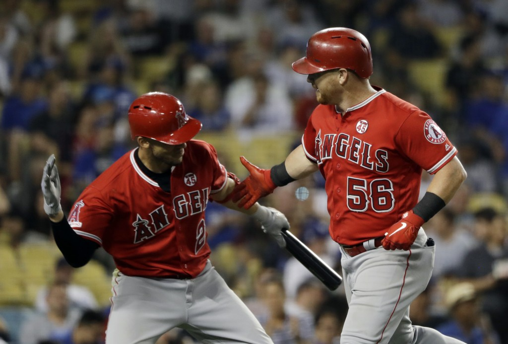 Los Angeles Angels' Kole Calhoun, right, celebrates his solo home run with teammate Andrelton Simmons during the seventh inning of a baseball game aga