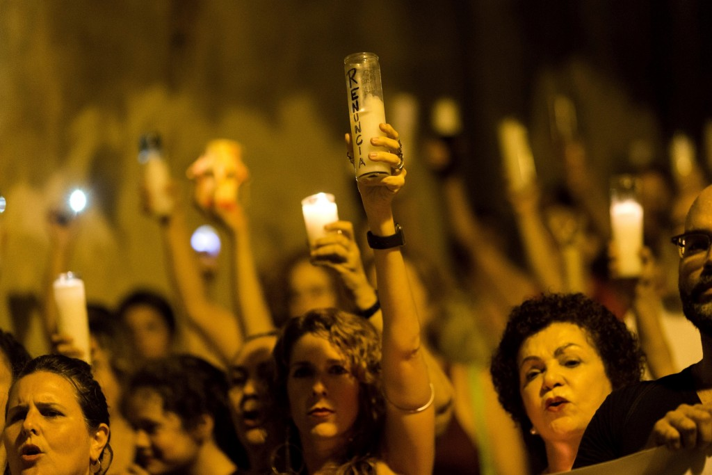 """People march with candles that have the word """"resign"""" written is Spanish, during a demonstration against Gov. Ricardo Rossello in San Juan, Puerto Ric..."""
