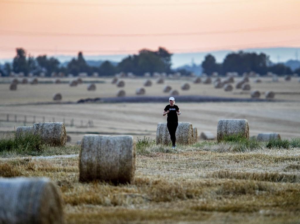 A woman runs along straw bales between fields in Frankfurt, Germany, early Wednesday, July 24, 2019. (AP Photo/Michael Probst)