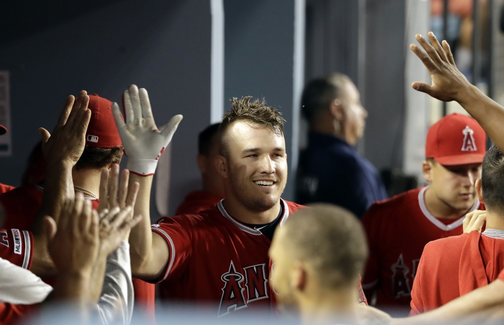 Los Angeles Angels' Mike Trout, center, celebrates his solo home run with teammates in the dugout during the fifth inning of a baseball game against t