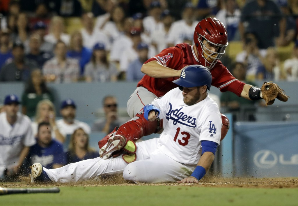 Los Angeles Dodgers' Max Muncy, bottom, scores past Los Angeles Angels catcher Dustin Garneau on an infield single by Russell Martin during the sixth