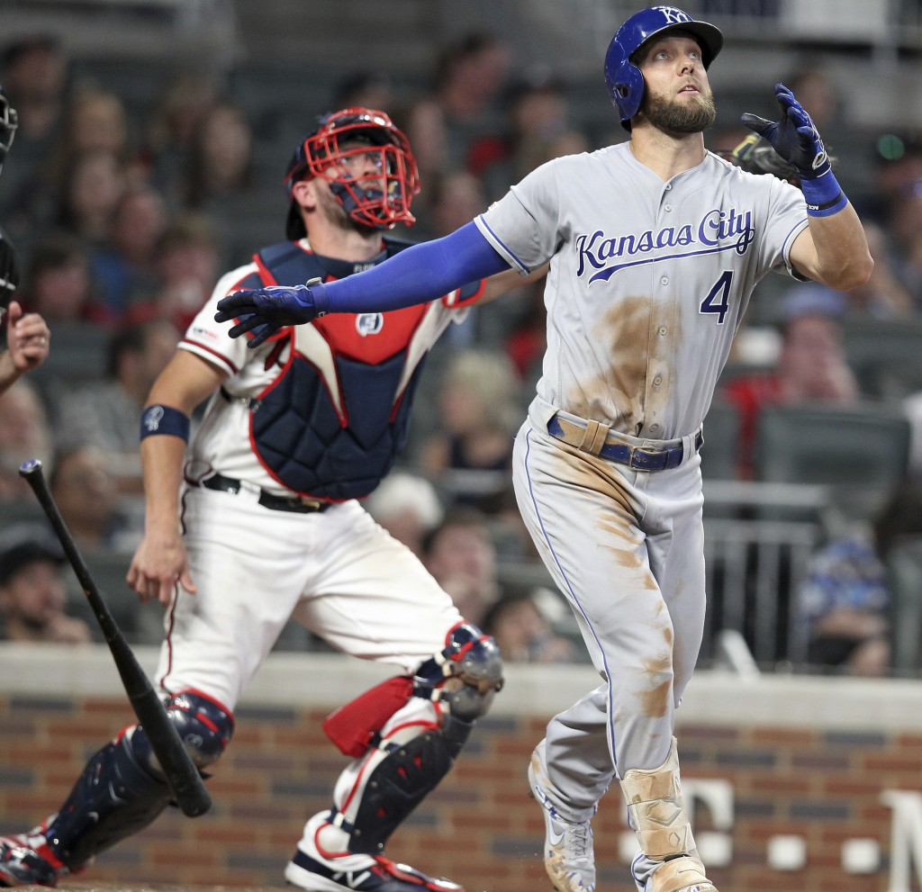 Kansas City Royals batter Alex Gordon watches his solo home run as Atlanta Braves catcher Tyler Flowers, left, looks on during the sixth inning of a b...