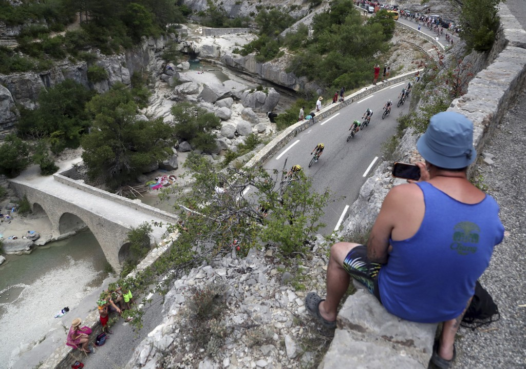 A man takes a pictures of the riders during the seventeenth stage of the Tour de France cycling race over 200 kilometers (124,27 miles) with start in ...