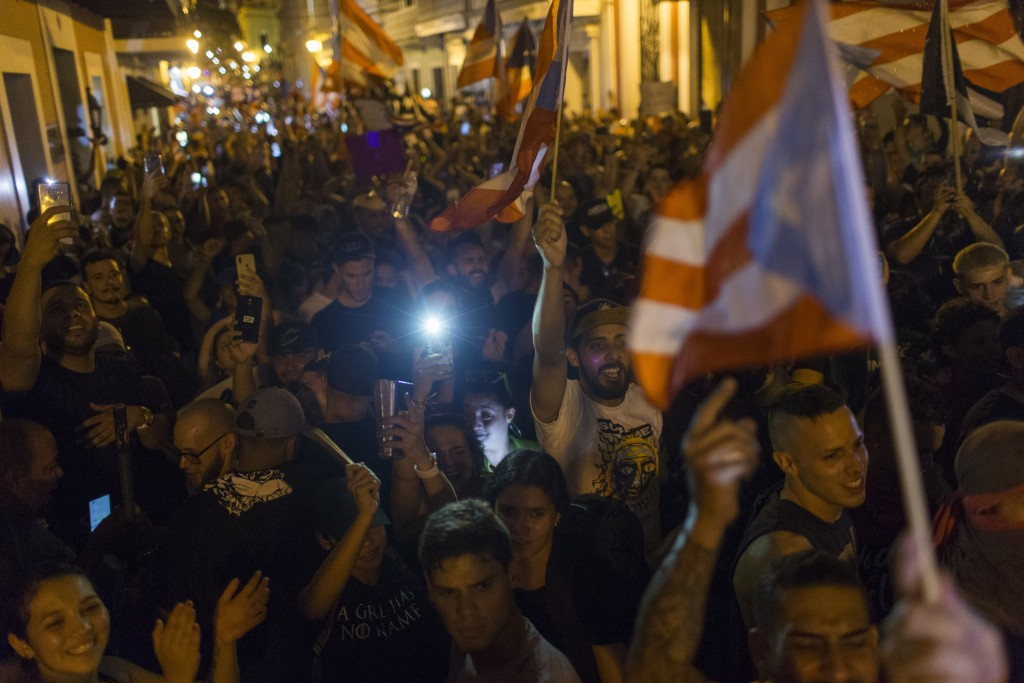 People celebrate outside the governor's mansion La Fortaleza, after Gov. Ricardo Rossello announced that he is resigning Aug. 2 after weeks of protest...
