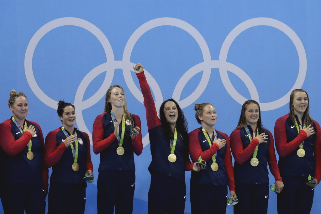 FILE - In this Aug. 19, 2016, file photo, members of the United States women's water polo team celebrate with their gold medals on the podium after wi...