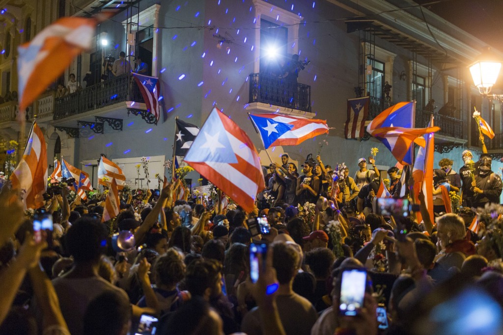 People celebrate outside the governor's mansion La Fortaleza, after Gov. Ricardo Rossello announced that he is resigning Aug. 2 after nearly two weeks...
