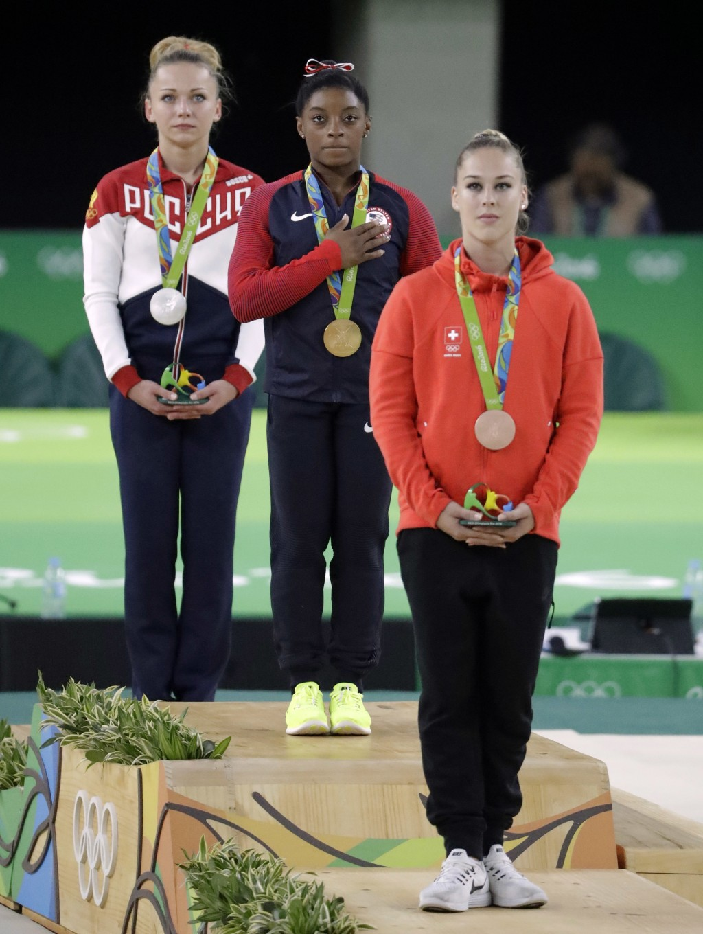 FILE - In this Sunday, Aug. 14, 2016 file photo, United States' Simone Biles, gold medal winner for vault, stands for her national anthem flanked by s...