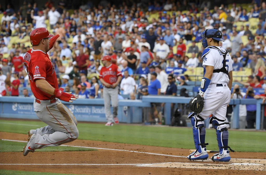 Los Angeles Angels' Mike Trout, left, scores on a double by Kole Calhoun as Los Angeles Dodgers catcher Austin Barnes stands at the plate during the f