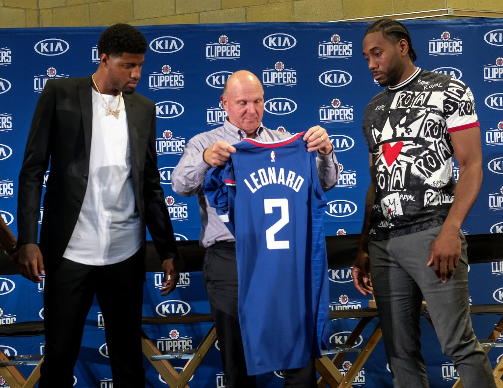 Los Angeles Clippers team chairman Steve Ballmer, center, presents a new team jersey to Kawhi Leonard, right, as Paul George looks on during a press c...