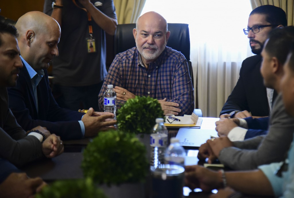 House leader Carlos Mendez Nunez, center, sits at the head of a table during an emergency meeting to discuss a report issued by a special committee ta...