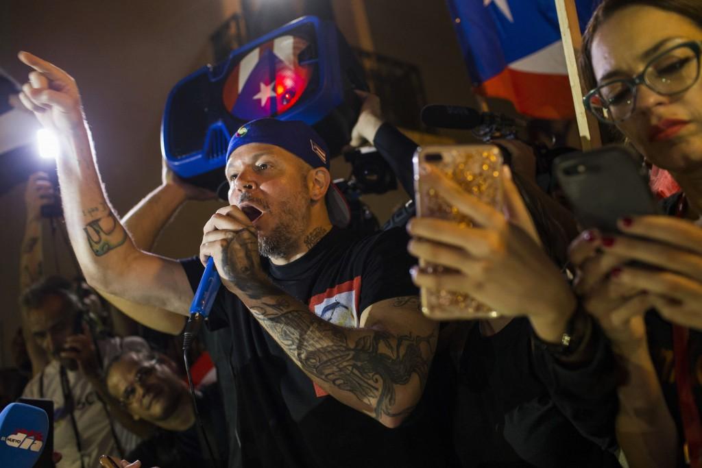 Singer Rene Perez Joglar celebrates outside the governor's mansion La Fortaleza, after Gov. Ricardo Rossello announced he is resigning Aug. 2, concedi...