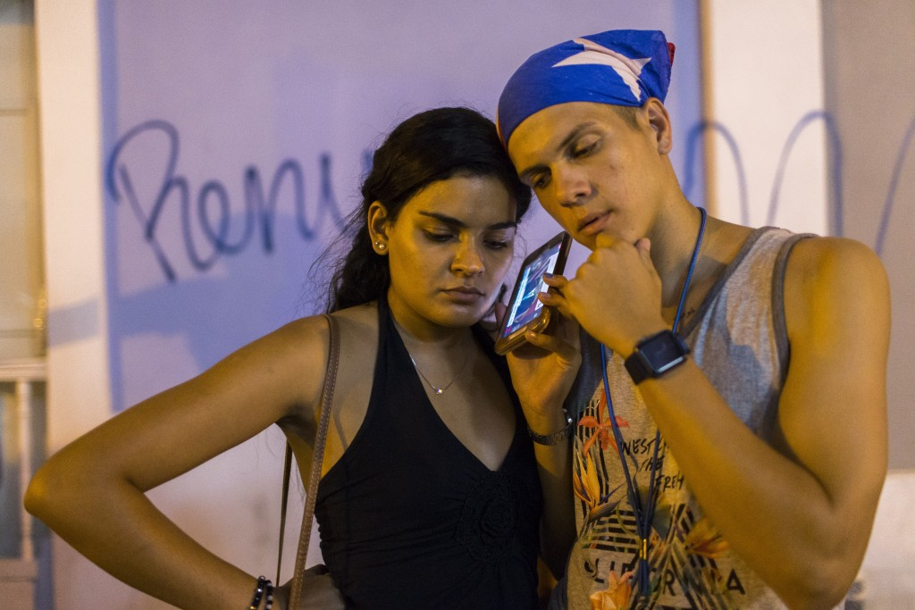 Locals listen on a smart phone to the pre-recorded message by Puerto Rico Gov. Ricardo Rossello announcing that he is resigning Aug. 2 after weeks of ...