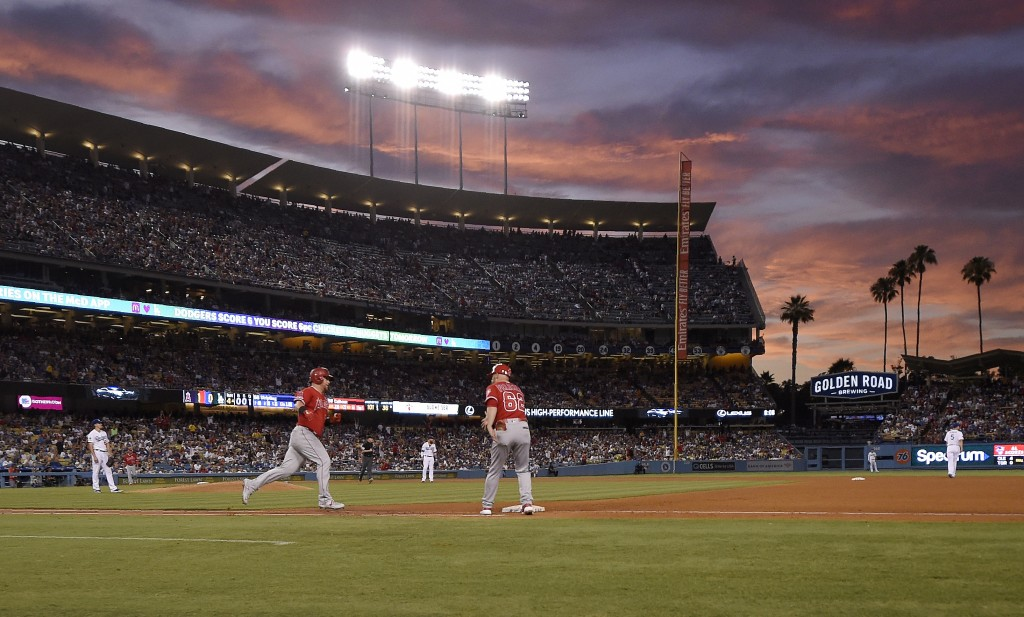 Los Angeles Angels' Kole Calhoun, second from left, rounds first after hitting a solo home run as Los Angeles Dodgers starting pitcher Ross Stripling,...