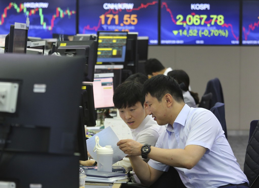 Currency traders watch documents at the foreign exchange dealing room of the KEB Hana Bank headquarters in Seoul, South Korea, Thursday, July 25, 2019