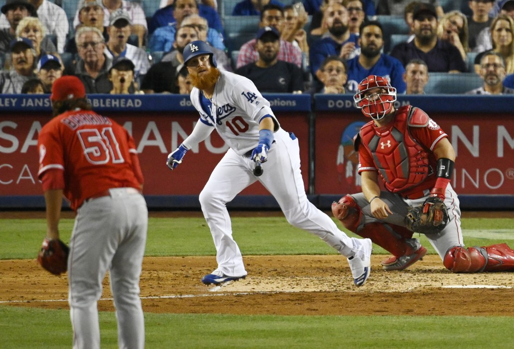 Los Angeles Dodgers' Justin Turner, center, hits a solo home run as Los Angeles Angels starting pitcher Jaime Barria, left, and catcher Kevan Smith wa