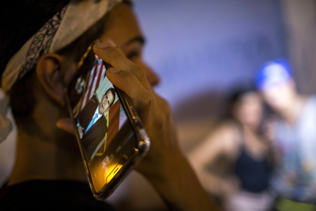 Locals listen on a smart phone to the pre-recorded message by Puerto Rico Gov. Ricardo Rossello announcing that he is resigning Aug. 2 after nearly tw...