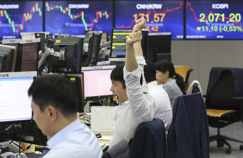 A currency trader stretches at the foreign exchange dealing room of the KEB Hana Bank headquarters in Seoul, South Korea, Thursday, July 25, 2019. Asi