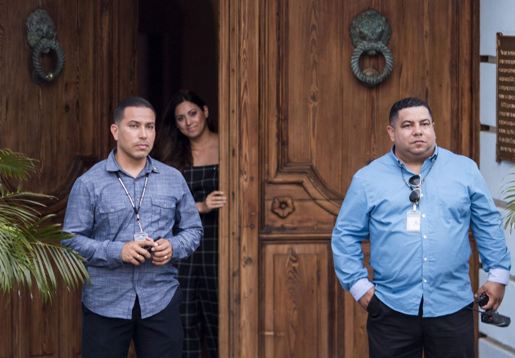 Puerto Rico's first lady Beatriz Rossello opens La Fortaleza Main Gate to let her dogs out, as two security men stand guard at La Fortaleza, the Gover...