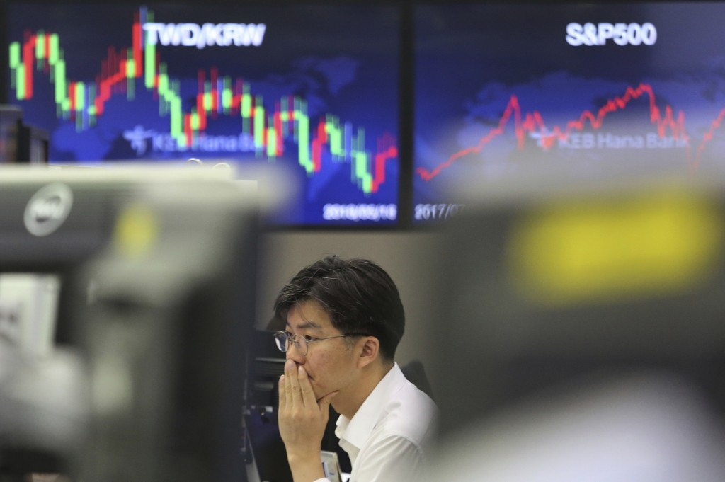 A currency trader watches monitors at the foreign exchange dealing room of the KEB Hana Bank headquarters in Seoul, South Korea, Thursday, July 25, 20