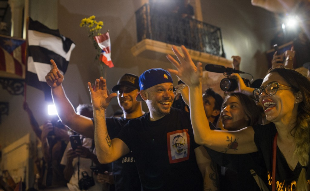 Singer Rene Perez Joglar celebrates outside the governor's mansion La Fortaleza, after Gov. Ricardo Rossello announced that he is resigning Aug. 2 aft...