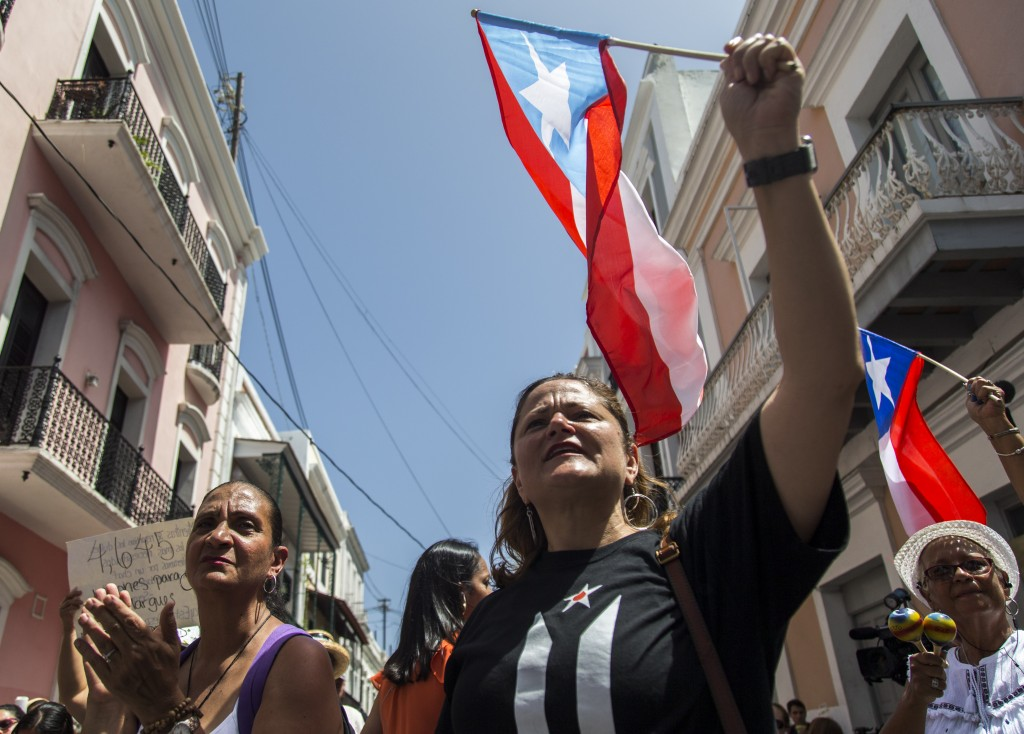 Ex-New York City councilwoman Melissa Mark-Viverito, center, joins protesters outside La Fortaleza, in San Juan, Puerto Rico, Wednesday, July 24, 2019...