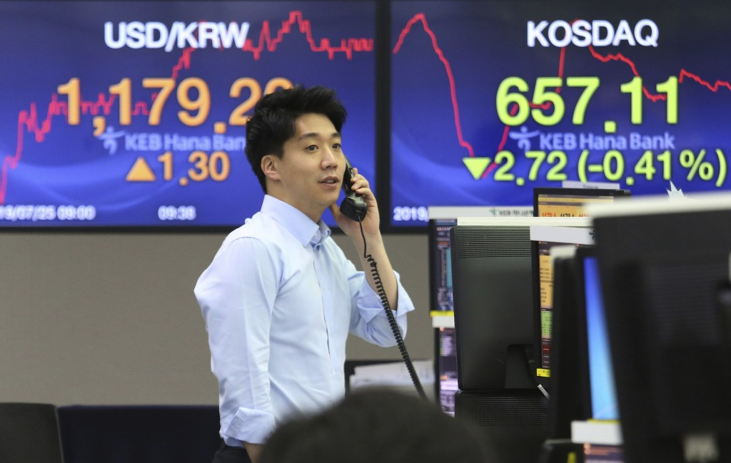 A currency trader talks on the phone at the foreign exchange dealing room of the KEB Hana Bank headquarters in Seoul, South Korea, Thursday, July 25,